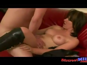 Horny brunette MILF wearing black knee boots gets fucked on the sofa while...