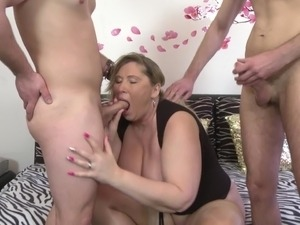 Mature busty mom takes two young cocks