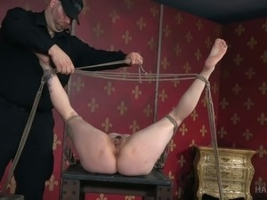 Brunette white lady bound and stretched on the wooden box